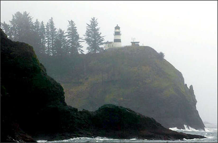 Low clouds shroud the coast as the Cape Disappointment Lighthouse flashes its beacon.  This was the kind of wet weather that the Lewis and Clark expedition found when they reached the Long Beach Peninsula in November 1805. Photo: Grant M. Haller, Seattle Post-Intelligencer