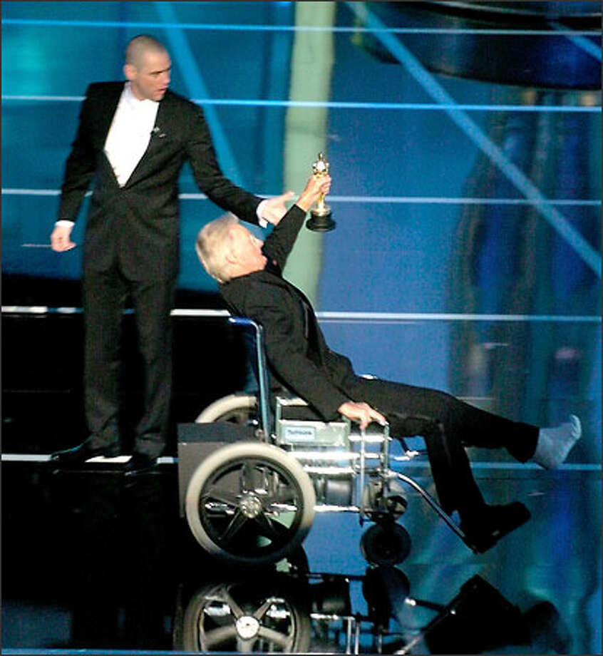 "Making an entrance, filmmaker Blake Edwards careens across the stage in an ""out-of-control"" wheelchair after grabbing his honorary Oscar from presenter Jim Carrey.  The stunt, evoking a memorable moment from the ""Pink Panther"" films, ended with Edwards crashing through the scenery. Photo: Associated Press"