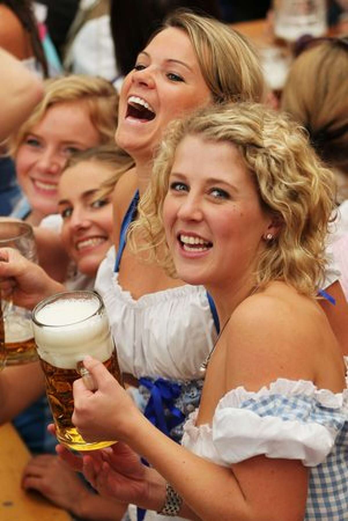 Girls toast with beer mugs during the opening day of the Oktoberfest at Theresienwiese in Munich, Germany.