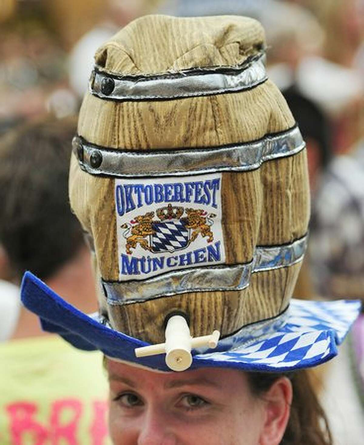 A young woman wears a hat featuring a beer barrel with a logo reading