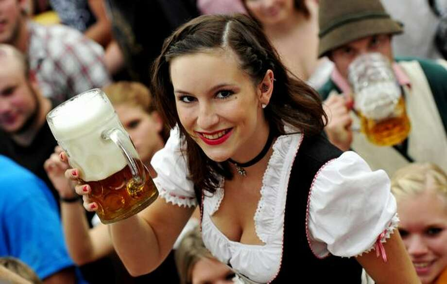 """A young woman wearing a traditiional Bavarian """"Dirndl"""" dress smiles as she receives a mug of beer in the Hofbraeuhaus-tent after the opening of the Oktoberfest beer festival at the Theresienwiese in Munich, southern Germany. Photo: Getty Images"""