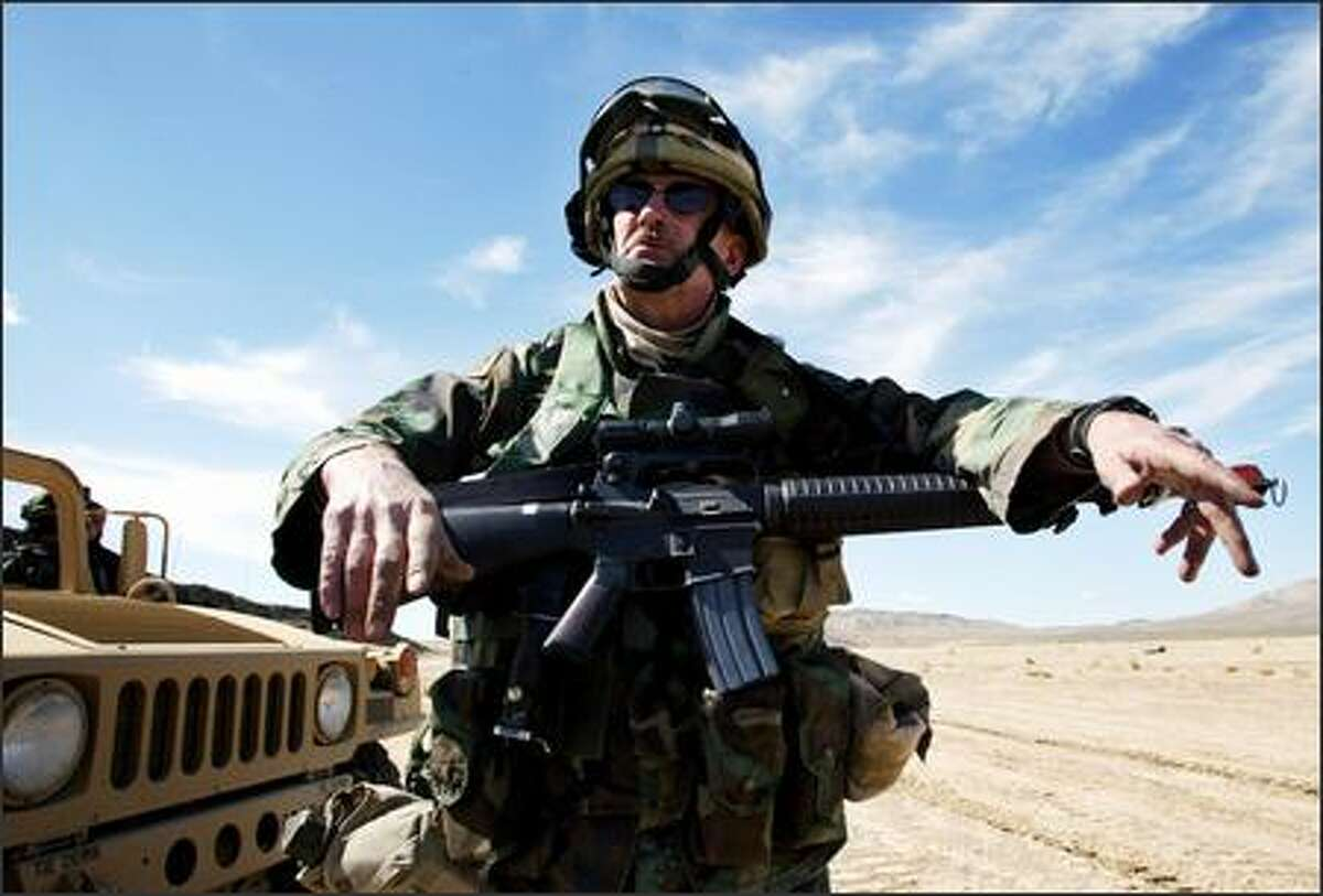 Sgt. Clarence Haubner, 55 from Olympia, with his M-16 equipped with a scope that his wife bought him just before he left. Haubner's 4-vehicle convoy was on a training exercise that included a stop to provide security for a radio relay station.