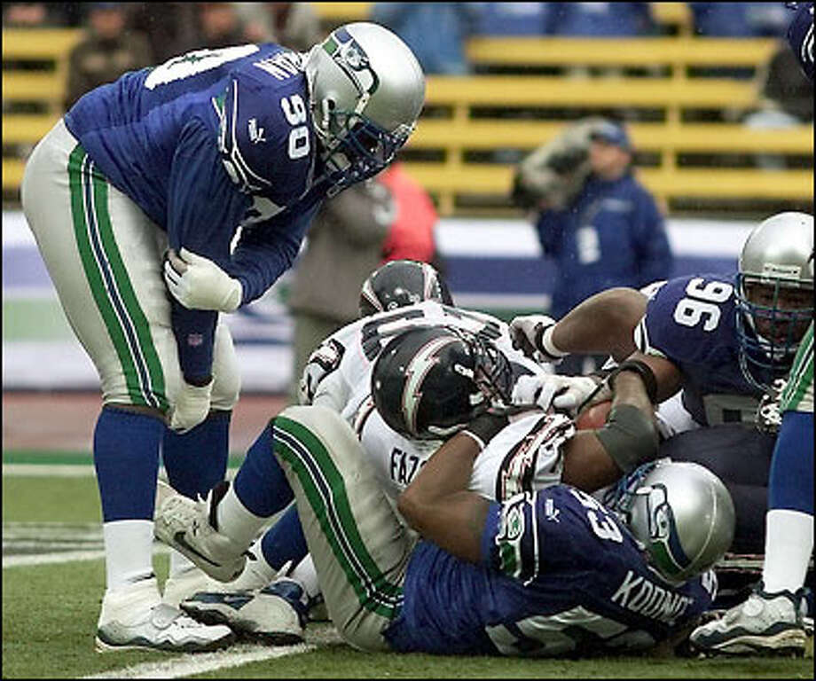 Running back Jermaine Fazande is held at the goal line by George Koonce (53) for no touchdown in the first half. San Diego settled for a field goal. Photo: Paul Kitagaki Jr., Seattle Post-Intelligencer
