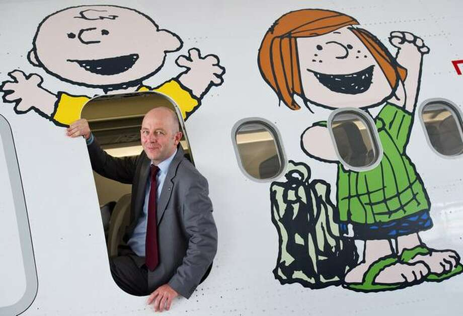 "Uwe Balser, chairman of German airline Condor, poses in the door of an airplane decorated with protagonists of the U.S. comic strip ""Peanuts"" on June 10, 2010 at the International Aerospace Exhibition at the Schoenefeld airport in Berlin. Photo: Getty Images"