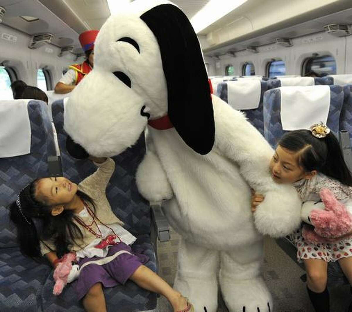 Cartoon character Snoopy greets children in the Shinkansen bullet train heading to Osaka from Tokyo for the promotion of Osaka based Hollywood theme park Universal Studios Japan on July 26, 2009.