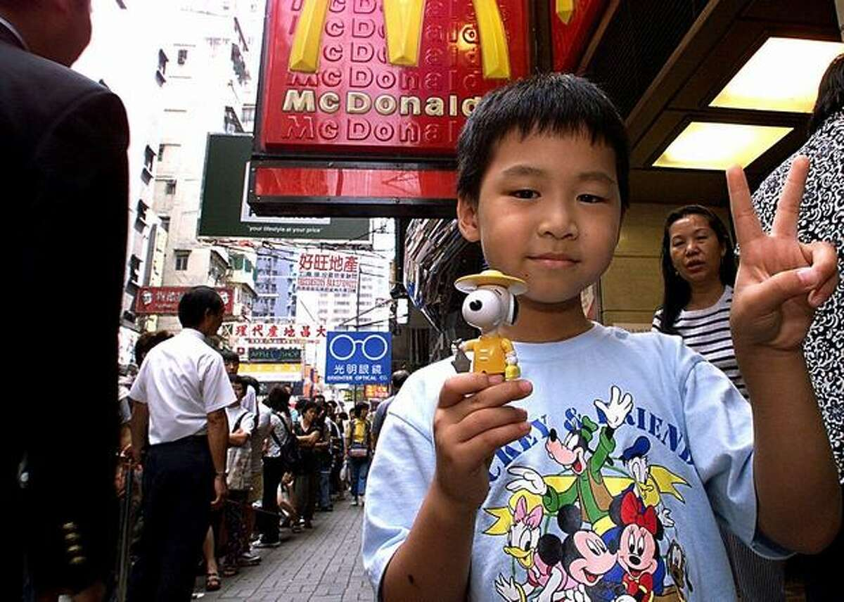 Seven-year-old Gary Lo shows off the Hong Kong McSnoopy doll (in the dress of a local fisherman) which he purchased when buying a McDonald's meal on Oct. 6, 1998. Large crowds have gathered since early morning as Hong Kong's mania for the small plastic Snoopy dolls has reached fever pitch with tens of thousands queuing to obtain the Hong Kong McSnoopy to add to the collection of 28 dolls in total.