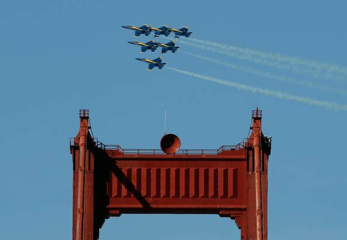 The U.S. Navy Blue Angels F/A-18 Hornets fly over the Golden Gate Bridge, in San Francisco while practicing for Fleet Week.