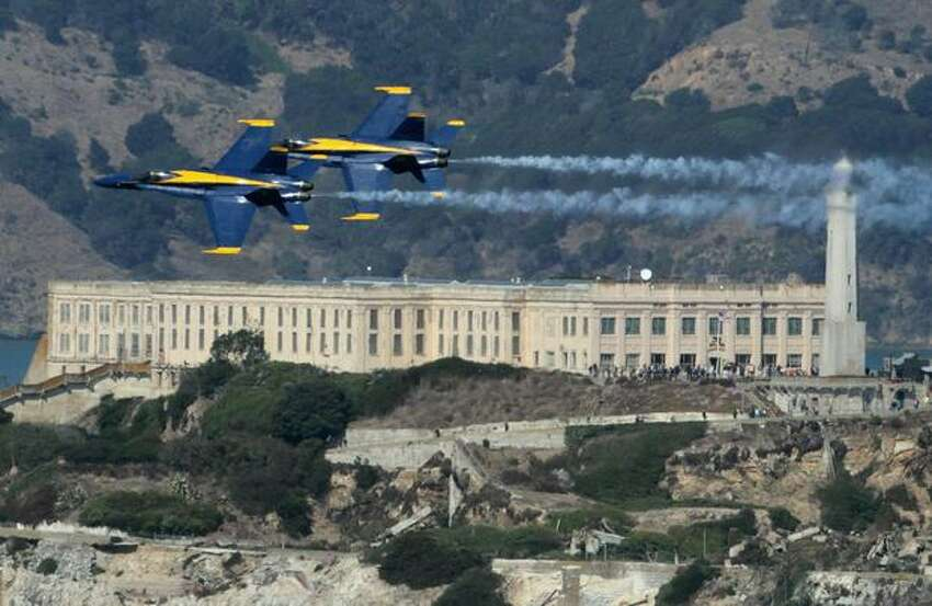 Two U.S. Navy Blue Angels F/A-18 Hornets fly over Alcatraz Island, in San Francisco while practicing for Fleet Week.