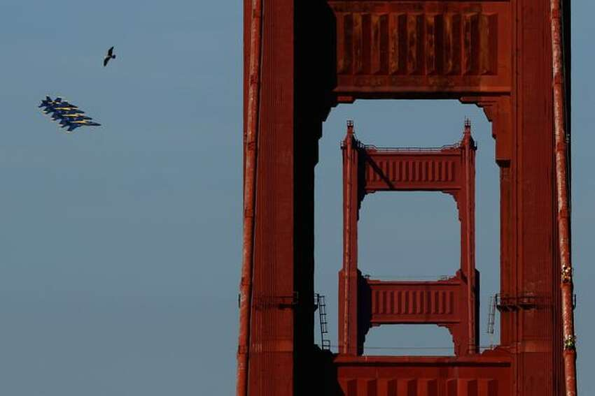 Navy Blue Angels F/A-18 Hornets fly past the Golden Gate Bridge, in San Francisco while practicing for Fleet Week.
