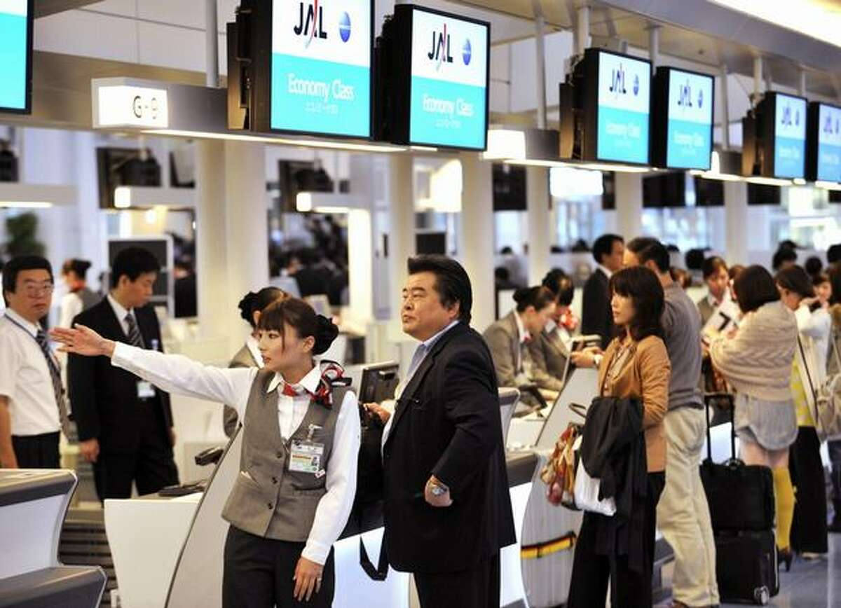 Passengers check in at an Japan Airlines desk at the newly opened international terminal building of the Tokyo International Airport.
