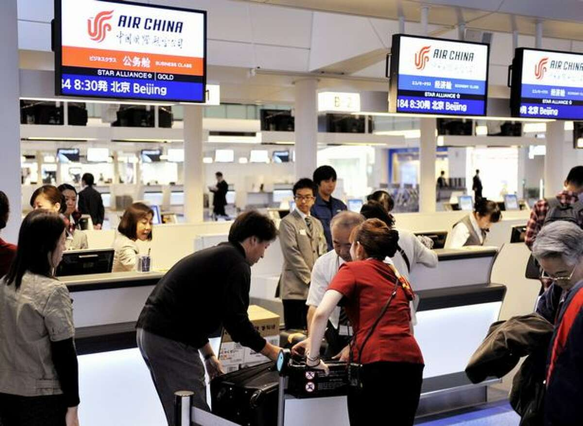 Passengers check in at an Air China desk at the newly opened international terminal building of the Tokyo International Airport.