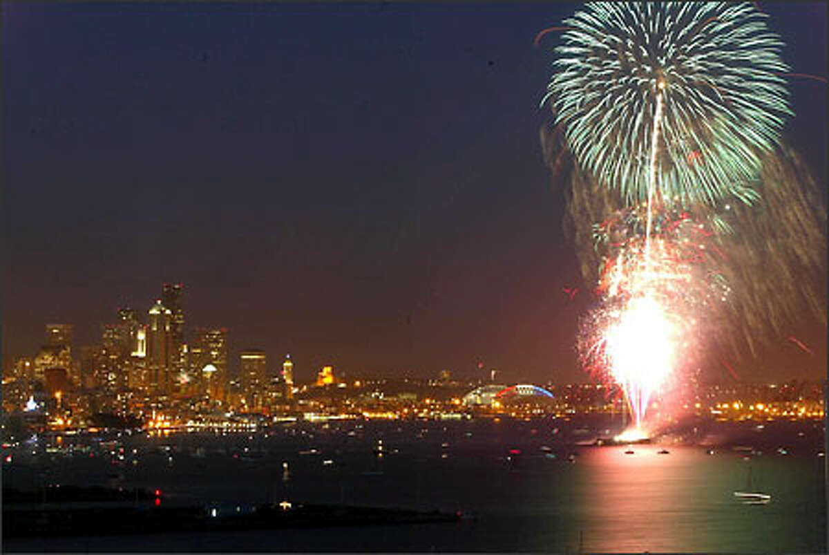 With the downtown Seattle skyline twinkling, fireworks explode over Elliott Bay one of the city's two major Fourth of July shows.