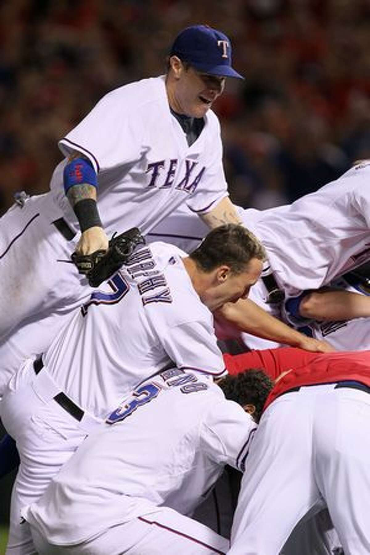 Top to bottom: Josh Hamilton #32, David Murphy #7 and Andres Blanco #3 of the Texas Rangers celebrate after defeating the New York Yankees 6-1 in Game Six of the ALCS to advance to the World Series during the 2010 MLB Playoffs at Rangers Ballpark in Arlington on Friday in Arlington, Texas.