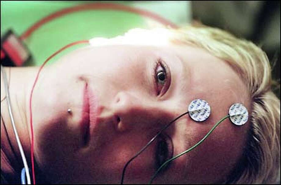 Electrodes attached, Melissa Greenlee undergoes auditory testing before cochlear implant surgery. Doctors think the device can put an end to her 15 years of deafness. Photo: Meryl Schenker, Seattle Post-Intelligencer