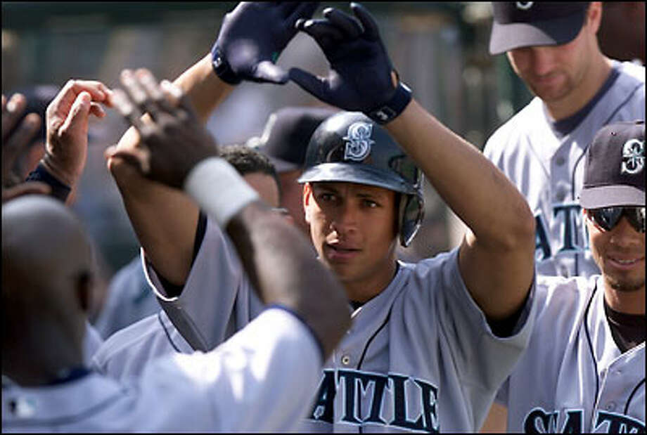 Alex Rodriguez is greeted after slugging a leadoff homer in the 4th inning to cut Anaheim's lead to 2-1. Photo: Paul Kitagaki Jr., Seattle Post-Intelligencer