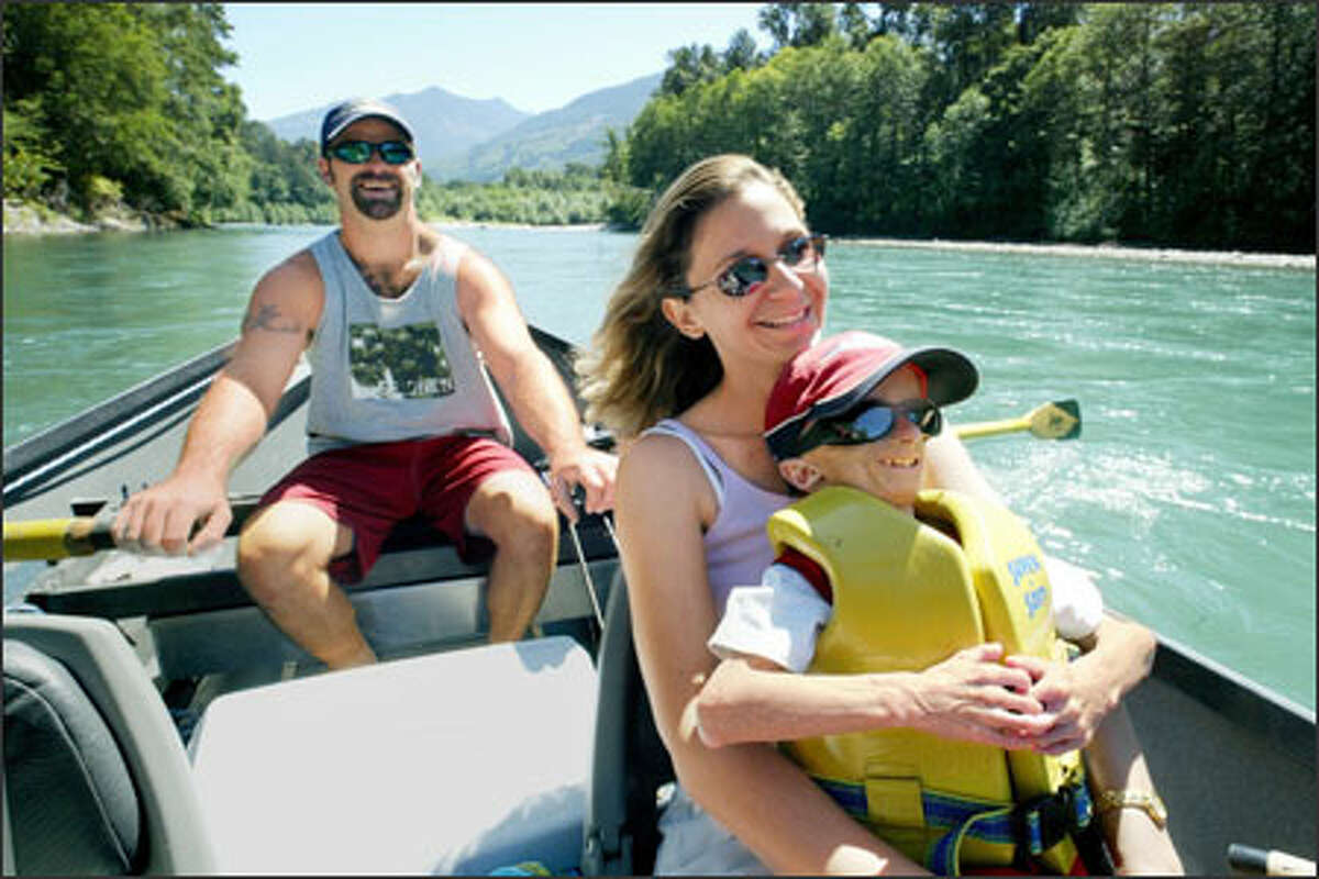 Kyle, Patti and Seth Cook float down the Skagit River in a drift boat while they fish for king salmon. River trips are regular outings for the family, and Seth has been catching fish since he was a toddler.