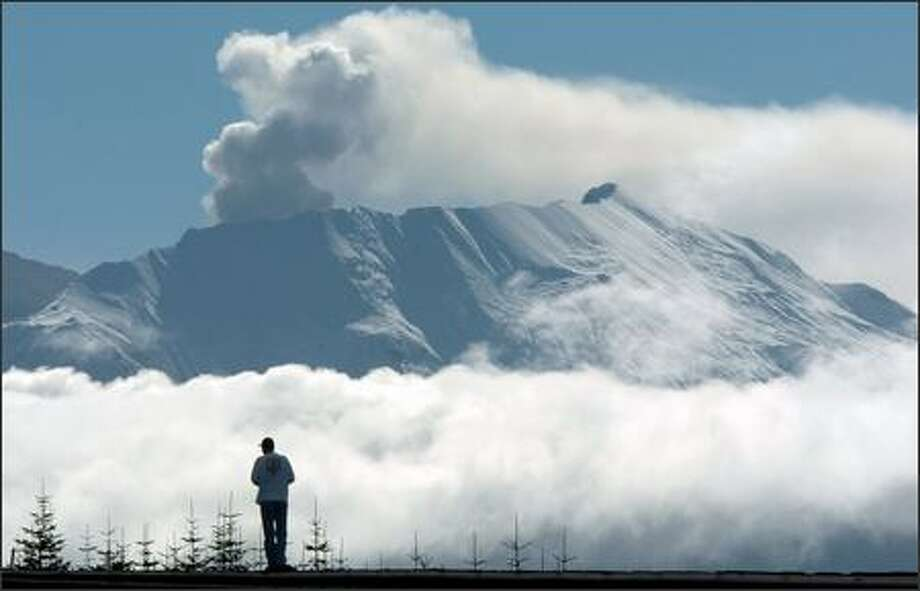 A volcano watcher stands on a roadside barrier to view the steam venting from the crater of Mount St. Helens near Toutle in Cowlitz County. The mountain is still drawing visitors. (AP Photo/Greg Wahl-Stephens) Photo: Associated Press