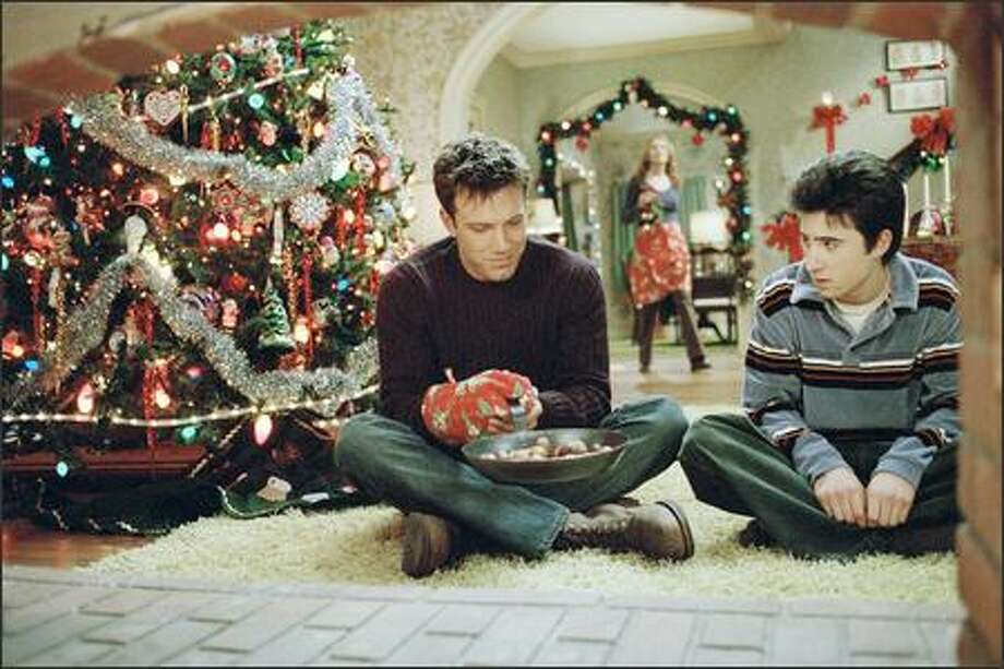 "Drew Latham (Ben Affleck, left) and his ""adopted"" brother Brian Valco (Josh Zuckerman) enjoy the old Christmas tradition of roasting chestnuts on an open fire, as their ""mother"" Christine (Catherine O'Hara) looks on. Photo: Dreamworks"
