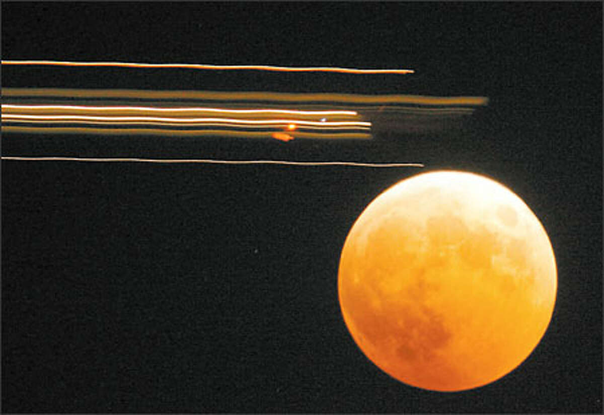 An airplane passes in front of the lunar eclipse as seen in this time lapse photo from West Seattle.