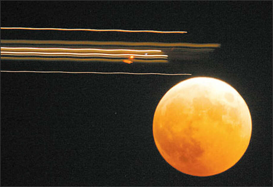 An airplane passes in front of the lunar eclipse as seen in this time lapse photo from West Seattle. Photo: Joshua Trujillo, Seattlepi.com