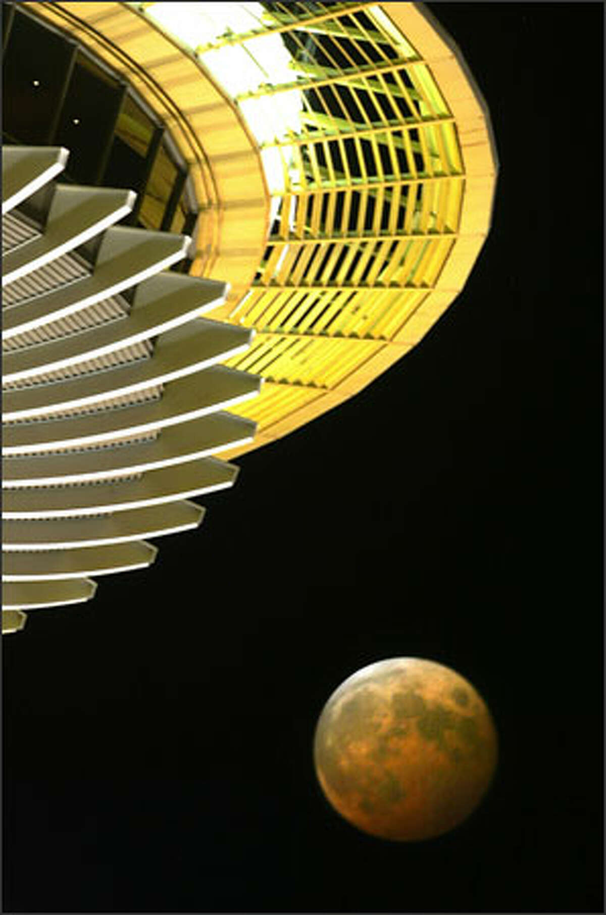 A total lunar eclipse is viewed from beneath the Space Needle. The celestial phenomenon, which occurs when the moon passes through the Earth's shadow and appears to turn dark orange, won't happen again until 2007. NASA says a total lunar eclipse gives scientists an opportunity to assess the quality of Earth's atmosphere. The more dust there is, the darker the moon.