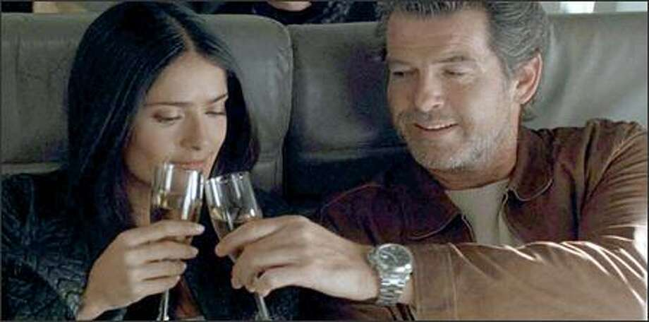 "Pierce Brosnan plays ""Max,"" a master thief, and Salma Hayek plays ""Lola,"" his girlfriend and accomplice. The film begins with Max and Lola escaping to a tropical paradise to enjoy the spoils of their labor. But when an FBI agent (Woody Harrelson), who has pursued them for seven years, becomes convinced that they are actually plotting to pull off a million-dollar theft from a nearby ""diamond cruise,"" a game of cat and mouse ensues. Photo: New Line Cinema"