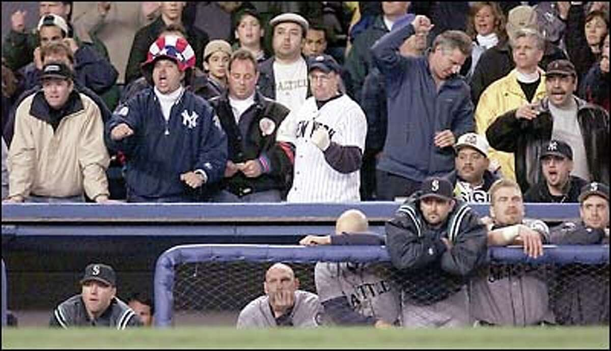 Yankees fans rejoice as they watch the Mariners' last at-bats. Their jubilation is not shared by Mariners watching from the dugout: (l-r) Brett Tomko, Jay Buhner, Raul Ibanez, Paul Abbott, Tom Lampkin and Dan Wilson.