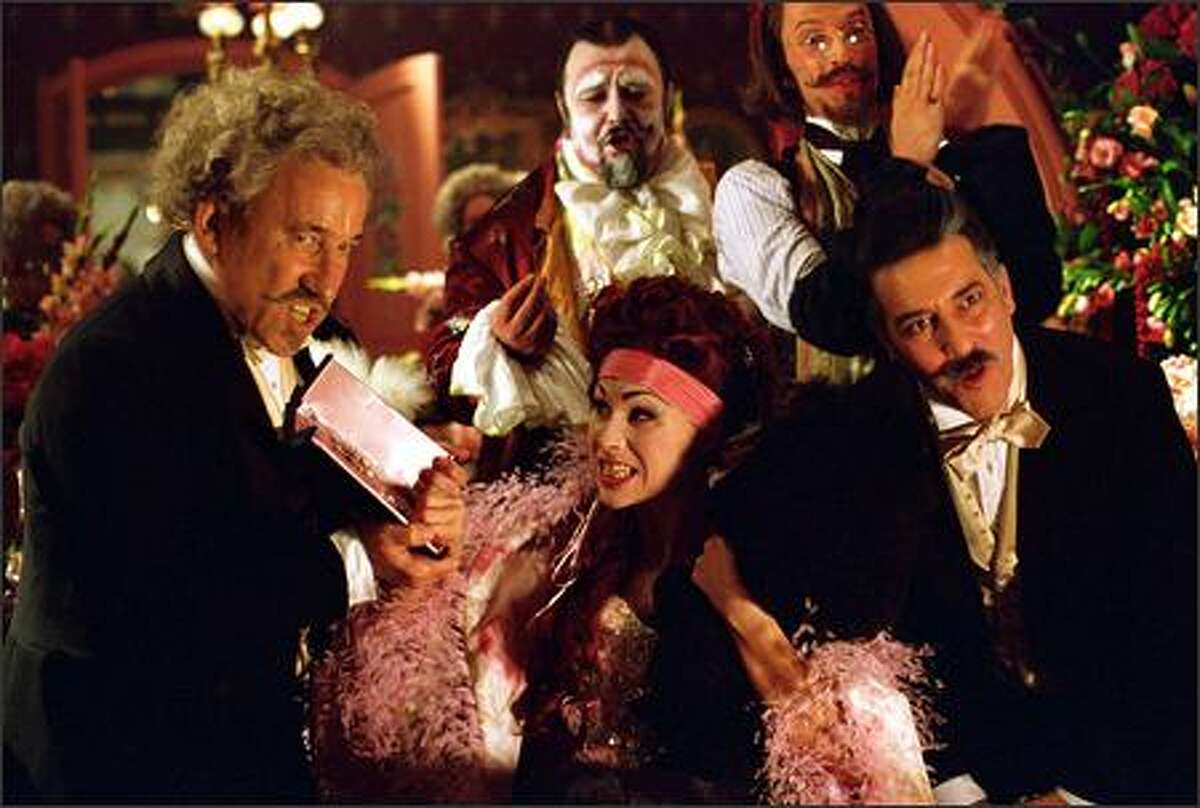 Beleaguered Opera Populaire managers Gilles Andre (Simon Callow, left) and Richard Firmin (Ciaran Hinds, right) try to appease their tempestuous diva, Carlotta (Minnie Driver, center).