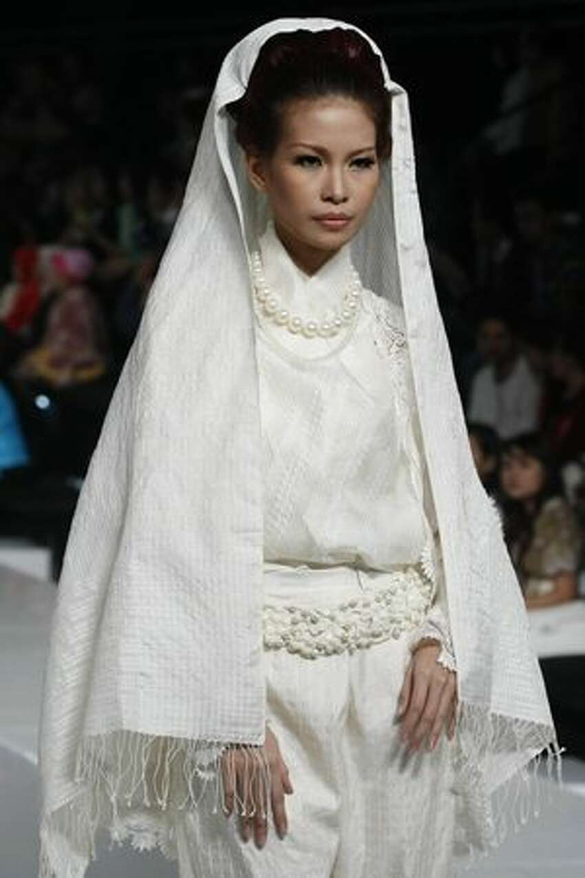 A model showcases designs on the runway by Ari Sista during the DEKRANASDA show on the second day of Jakarta Fashion Week in Jakarta, Indonesia.