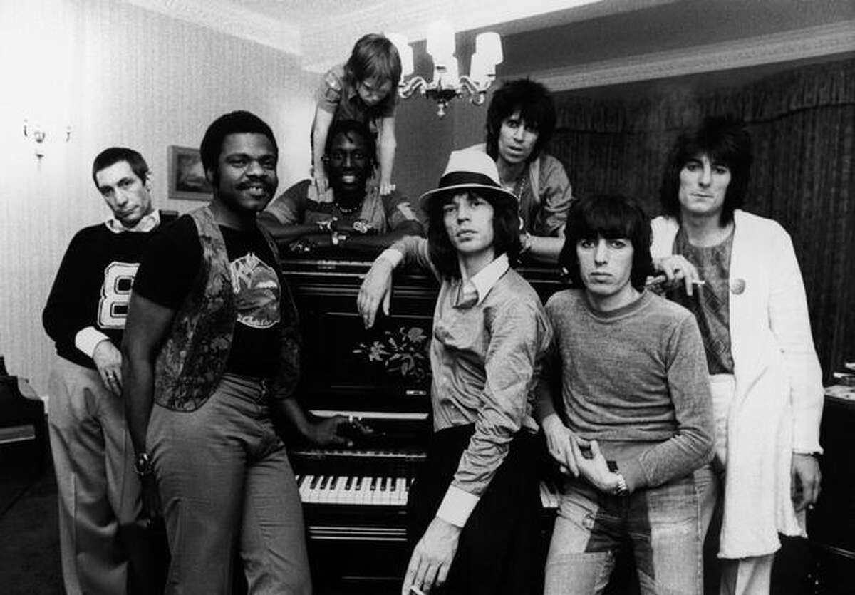 The Rolling Stones together in their hotel at 2 a.m. after a British concert, 19th May 1976. Accompanying the group on tour is Keith Richards' 6-year-old son Marlon. Left to right: Charlie Watts, keyboard player Billy Preston, percussionist Ollie Brown with Marlon Richards, Mick Jagger, Keith Richards, Bill Wyman and Ron Wood.