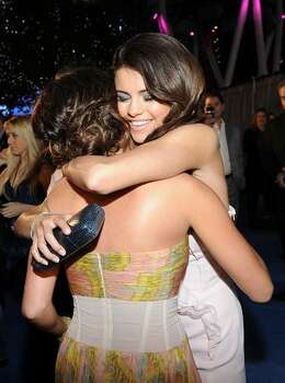 Actress Ashley Tisdale (L) and singer Selena Gomez arrive at the 2011 People's Choice Awards at Nokia Theatre L.A. Live in Los Angeles, California. Photo: Getty Images