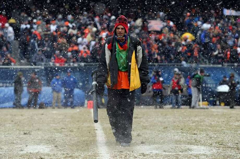 CHICAGO, IL - JANUARY 16: A member of the field crew blows the snow off the yardage lines in the second quarter of the 2011 NFC divisional playoff game between the Seattle Seahawks and the Chicago Bears at Soldier Field on January 16, 2011 in Chicago, Illinois. Photo: Getty Images