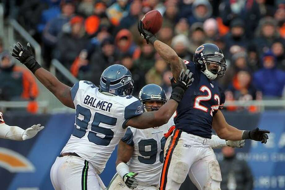 CHICAGO, IL - JANUARY 16: Running back Matt Forte #22 of the Chicago Bears throws a pass over the arm of Kentwan Balmer #95 of the Seattle Seahawks as the pass is intercepted by Aaron Curry #59 in the second half of the 2011 NFC divisional playoff game at Soldier Field on January 16, 2011 in Chicago, Illinois. Photo: Getty Images