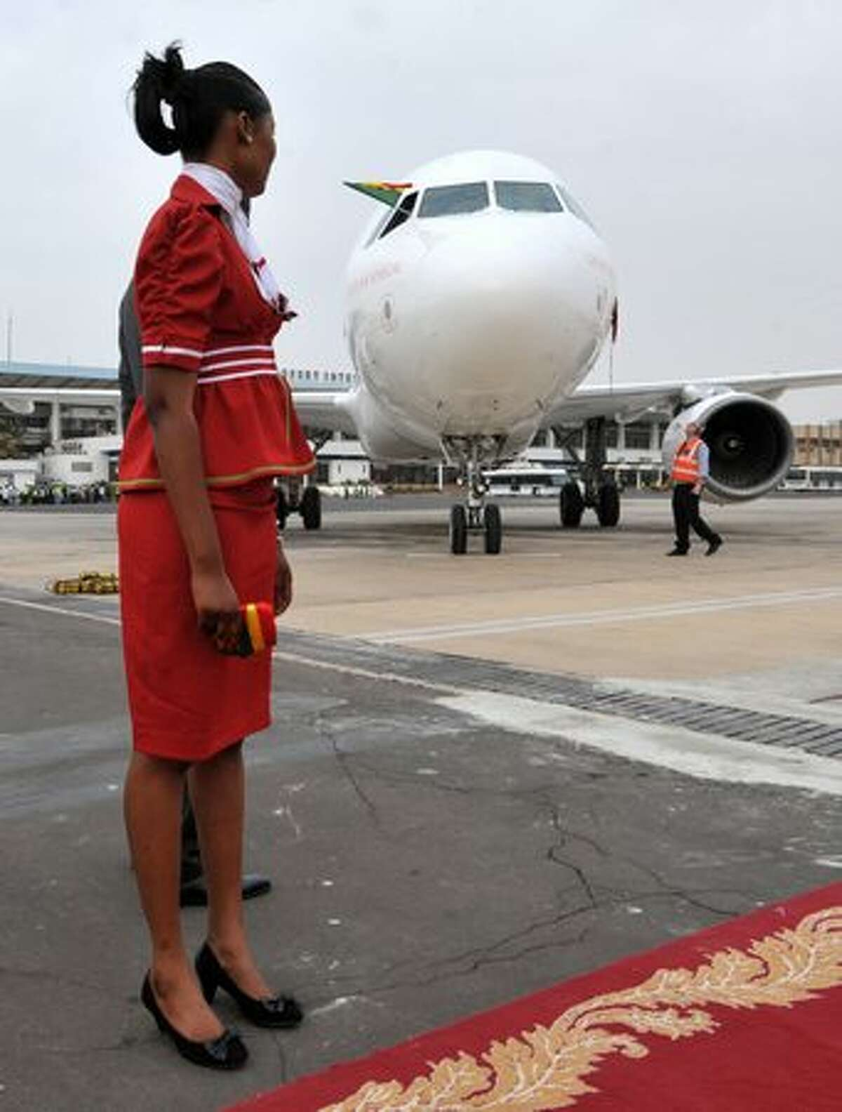 A flight attendant stands in front of a Senegal Airlines Airbus A320 in Dakar. The airline plans to launch its first flight on January 25, 2011.