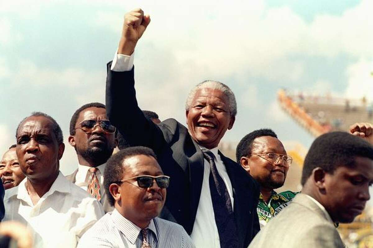 South African National Congress (ANC) President Nelson Mandela gives 15 March 1994 a clenched fist to supporters upon his arrival for his first election rally for 27 April general elections.