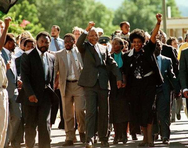 PAARL, SOUTH AFRICA: South African National Congress (ANC) President Nelson Mandela (c) and his then-wife Winnie raise their fists 11 February 1990 in Paarl to salute cheering crowd upon Mandela's release from Victor Verster prison. Photo: Getty Images