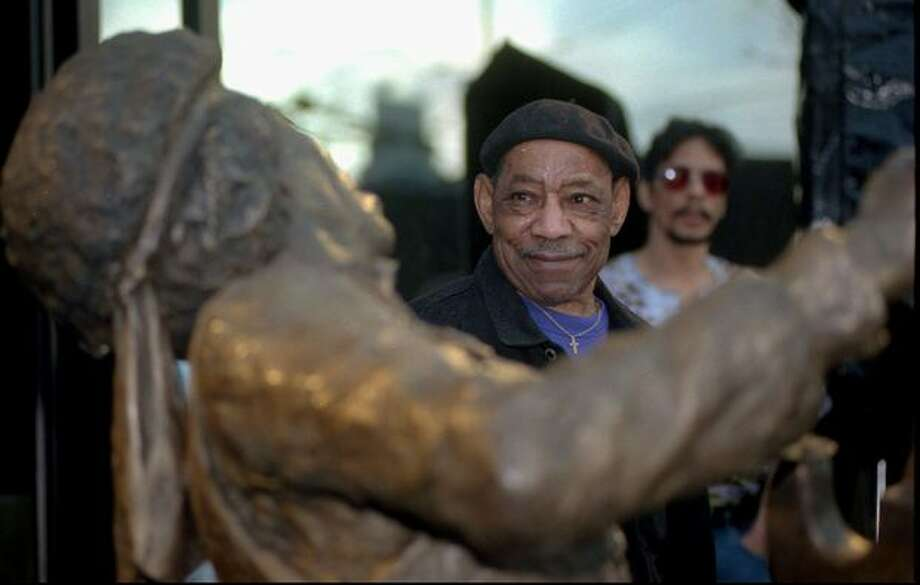 """Al Hendrix, father of the late guitarist Jimi Hendrix, views a bronze statue of his son at an unveiling ceremony Tuesday, Jan. 21, 1997, outside the corporate offices of AEI Music in Seattle. AEI Music commissioned the statue to memorialize Hendrix's 1970 Fender Stratocaster guitar, which AEI owned, as part of their """"Legends Collection"""" of music memorabilia. (AP Photo/Robert Sorbo)"""