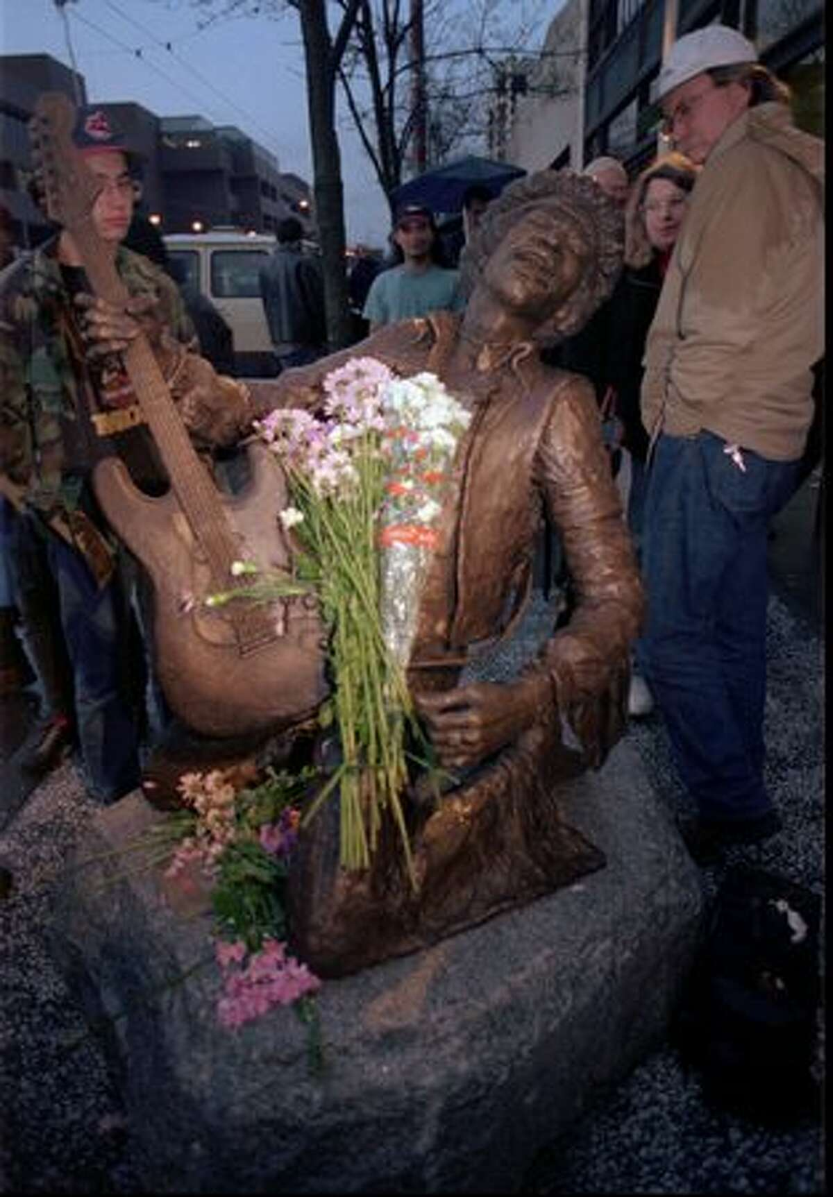 Fans view a bronze statue of the late guitarist Jimi Hendrix at an unveiling ceremony Tuesday, Jan. 21, 1997, outside the corporate offices of AEI Music in Seattle. AEI Music commissioned the statue to memorialize Hendrix's 1970 Fender Stratocaster guitar, which AEI owned, as part of their
