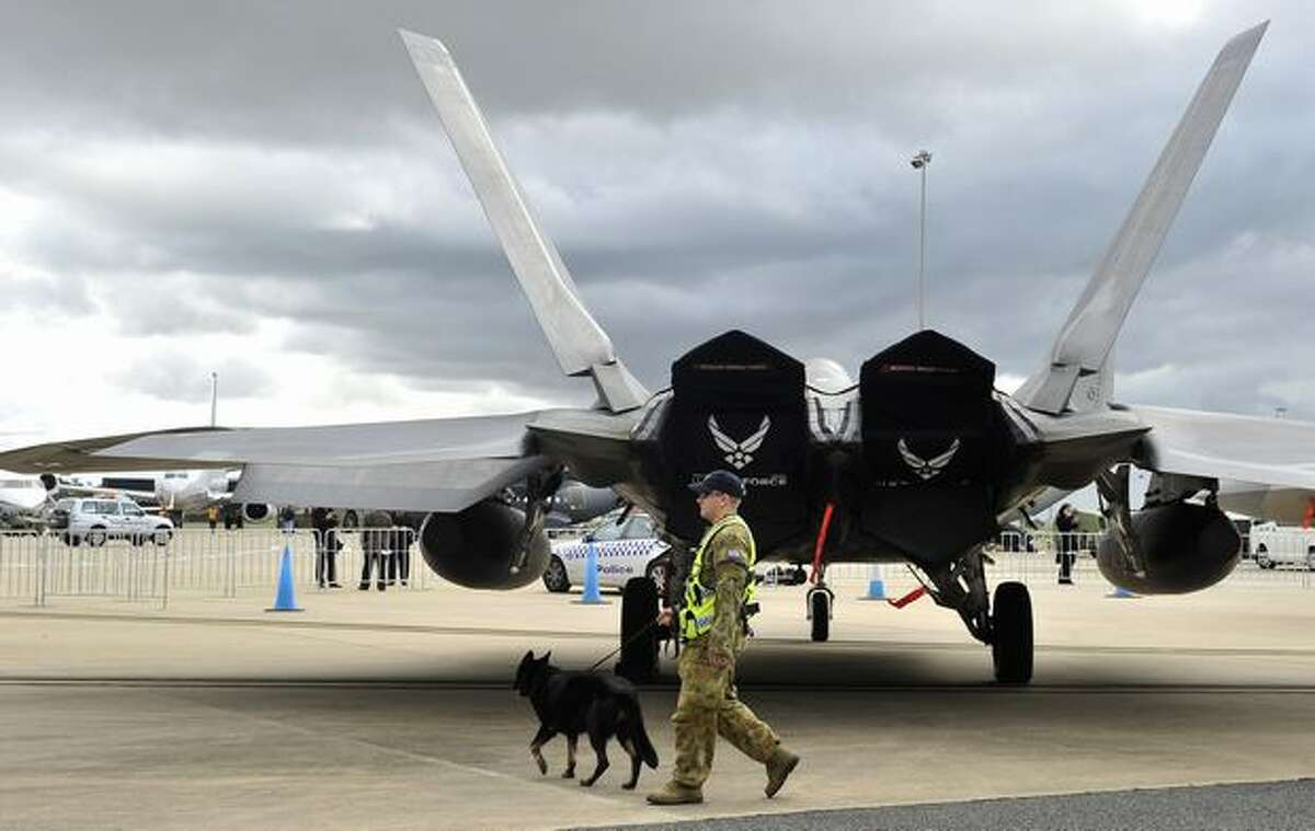 A member of the Royal Australian Air Force guards a U.S. Air Force F-22 fighter jet at the Australian International Airshow and Aerospace & Defence Expo in Melbourne.