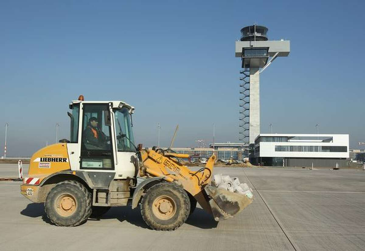 A digger drives past the control tower at the main terminal of the new Airport Berlin Brandenburg International BBI in Schoenefeld, Germany. The airport, which will replace Berlin's current Tegel and Schoenefeld airports, will have a capacity of 25 million passengers and is scheduled for completion in June 2012.