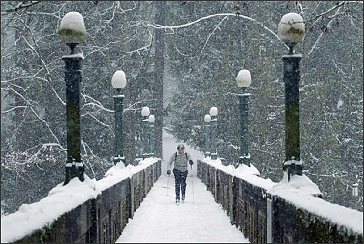 Under heavy snowfall, Paul Milan cross country skis on a footbridge spanning Lake Washington Boulevard in Montlake. Milan skied from his home on Capitol Hill.