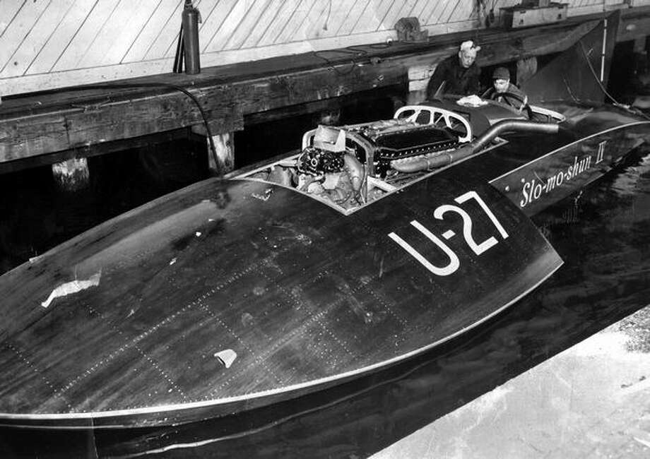 The 1950 P-I caption read: Stan Sayres' Slo Mo Shun IV was put in to water Monday after a thorough going-over. In this photo, Anchor Jensen sits at the controls while Sayres looks on during motor tuneups at Jensen plant, Portage Bay. Photo: P-I File