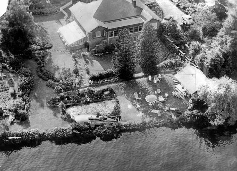 The Gale IV hydroplane crashed into the front yard of Dr. F. A. Black, 1500 Lakeside Ave. S., after a mishap during the second heat of the 1954 Gold Cup race on Lake Washington. Note people on the lawn at right who were startled to have the fast-moving boat come roaring ashore so close to where they sat watching the Seafair race. Photo: P-I File