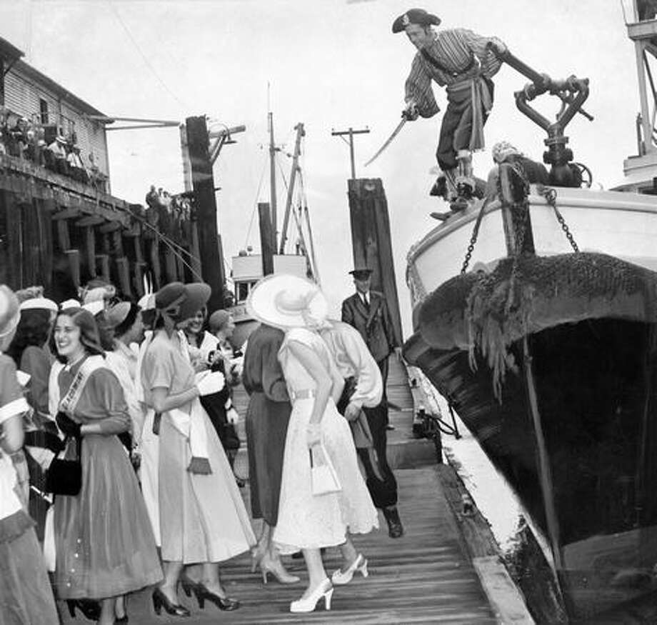 The August 1950 P-I caption read: A Seafair Pirate, with Cutlass in hand, prepares to jump to the pier from the harbor patrol boat which brought in Davy Jones and his no-good crew to bedevil the beautiful women on the dock at the foot of Washington Street. Photo: P-I File