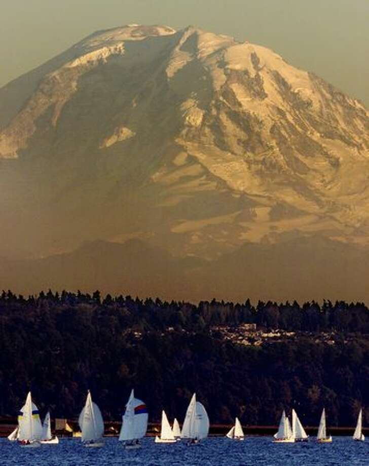Sailboats, dwarfed by Mount Rainier, dodge in and out of the last shadows of the day at sunset on August 22, 2000. Photo: P-I File