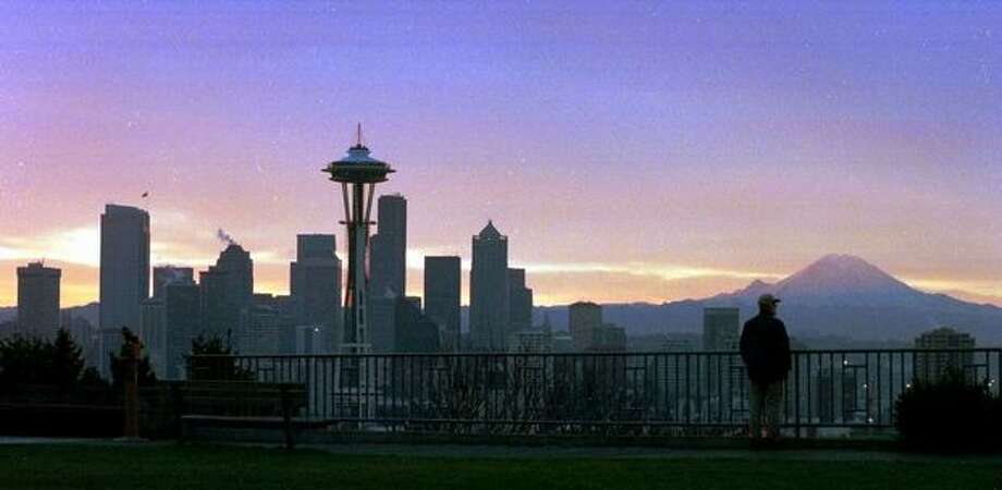 The sunrise in Seattle on Jan. 13, 1999 gave this view of the skyline with the Space Needle and Mount Rainier.  (AP Photo/Barry Sweet) Photo: P-I File