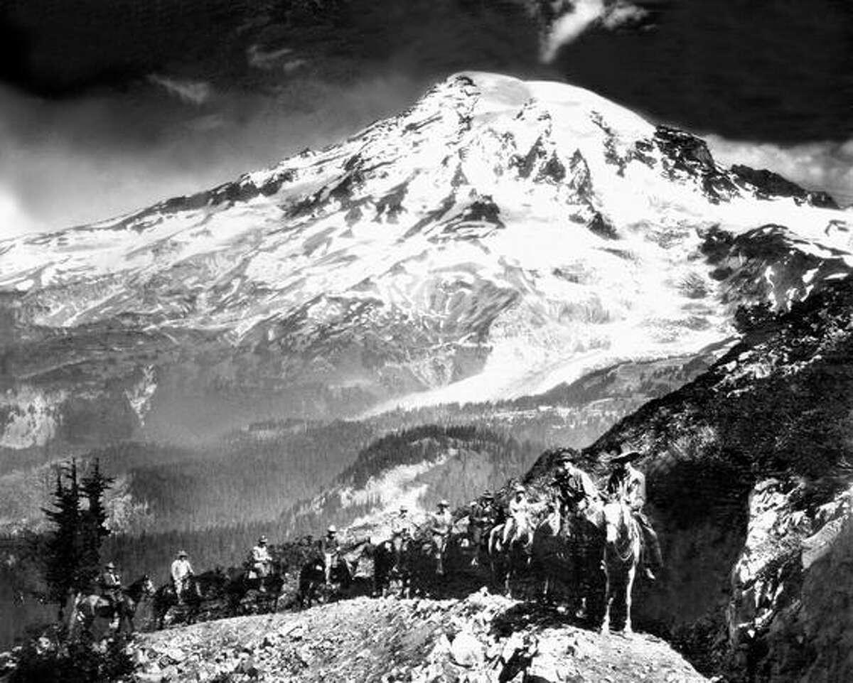 Riders and their mounts ride along Tatoosh Range to Pinnacle Peak saddle, Mount Rainier.