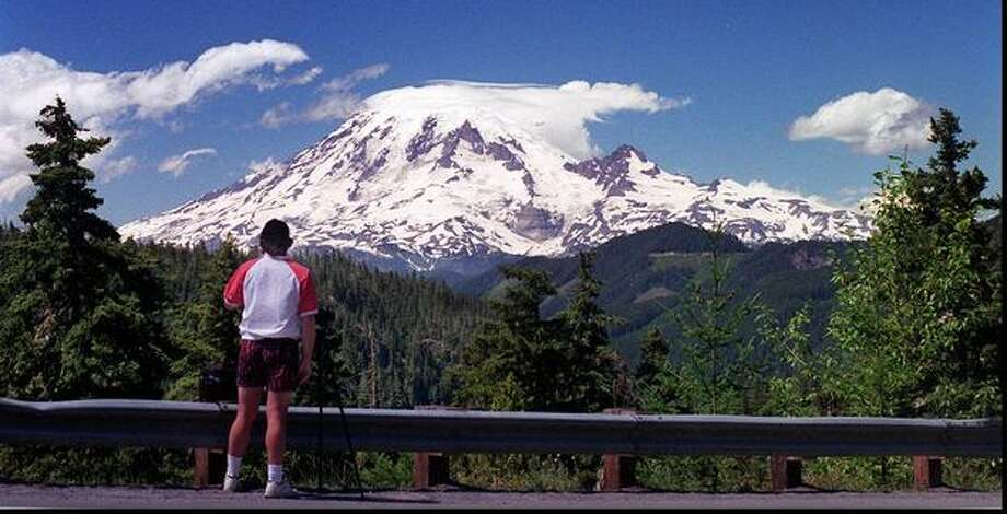 John Roberson, of Spokane, stops along U.S. Highway 12 to photograph clouds and Mount Rainier on July 28, 1995. (Grant M. Haller/P-I) Photo: P-I File