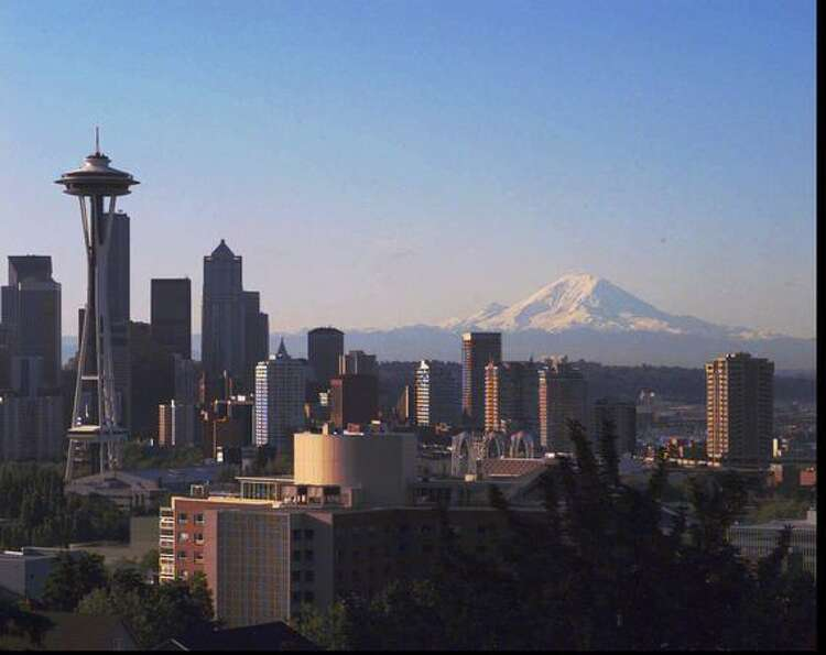 The skyline of Seattle sits under a towering Mount Rainier on July 12, 1995. (AP Photo/Barry Sweet)