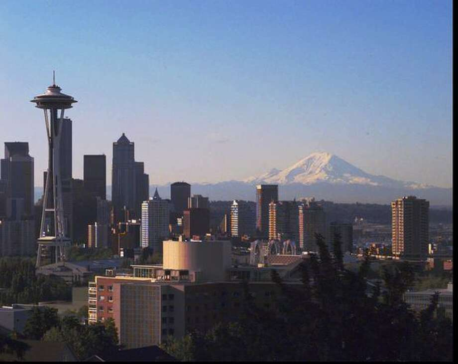The skyline of Seattle sits under a towering Mount Rainier on July 12, 1995. (AP Photo/Barry Sweet) Photo: P-I File